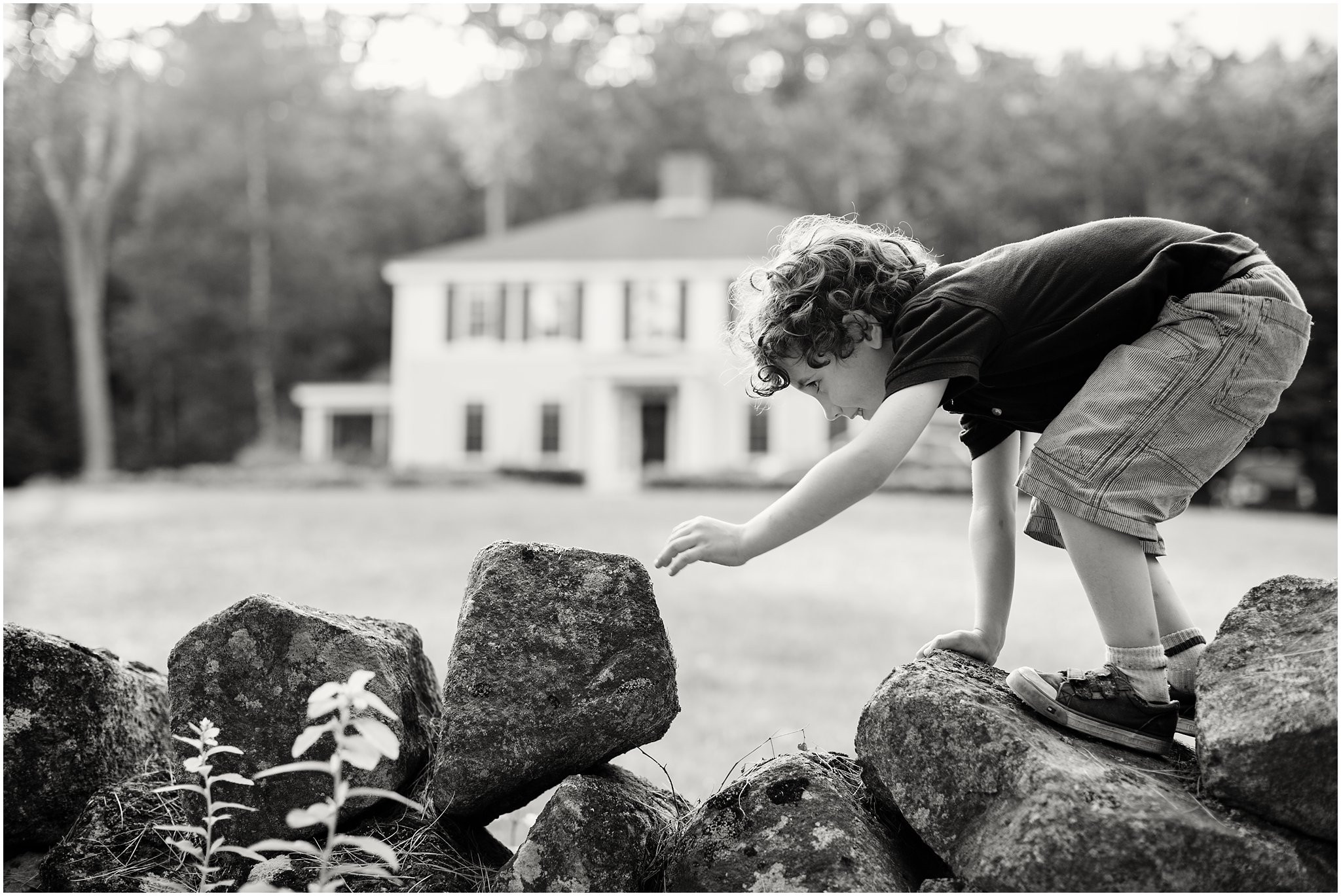 black and white photo of boy climbing stone wall