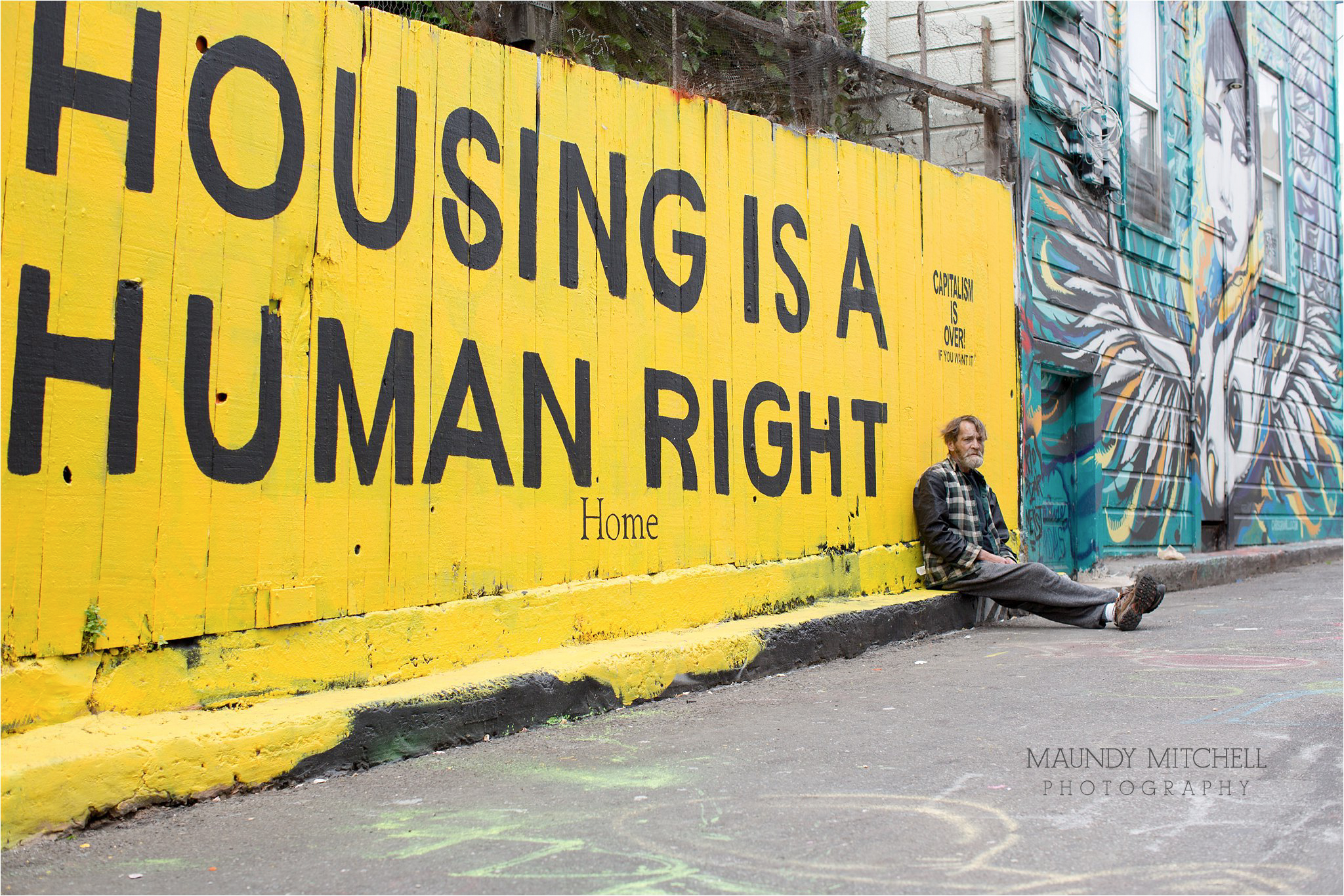 Homeless Man Sitting by Human Rights Mural