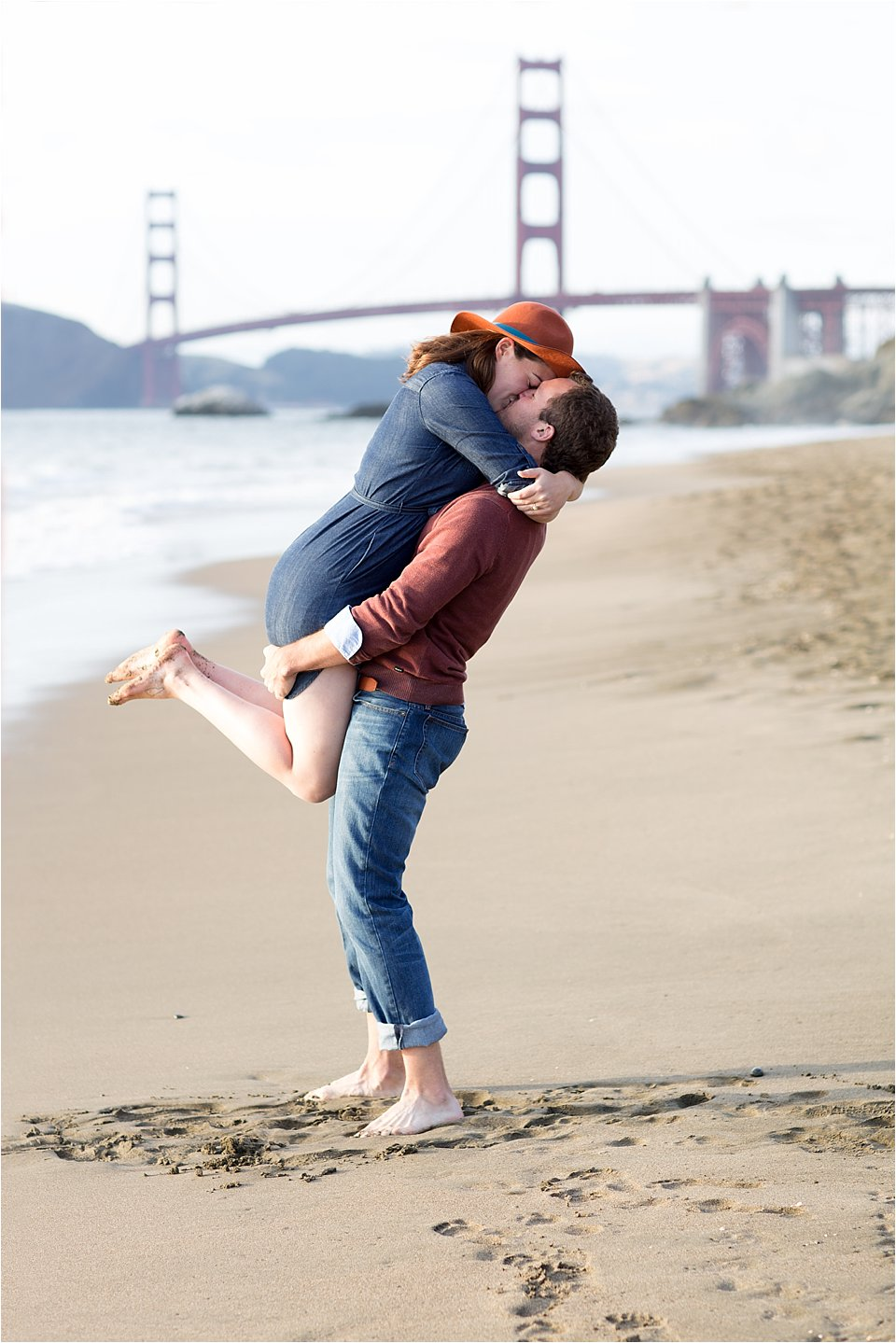 Joyful Engaged Couple on Beach With View of Golden Gate Bridge