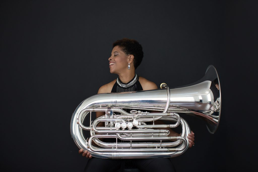 Profile of tuba player Velvet Brown holding a tuba and laughing