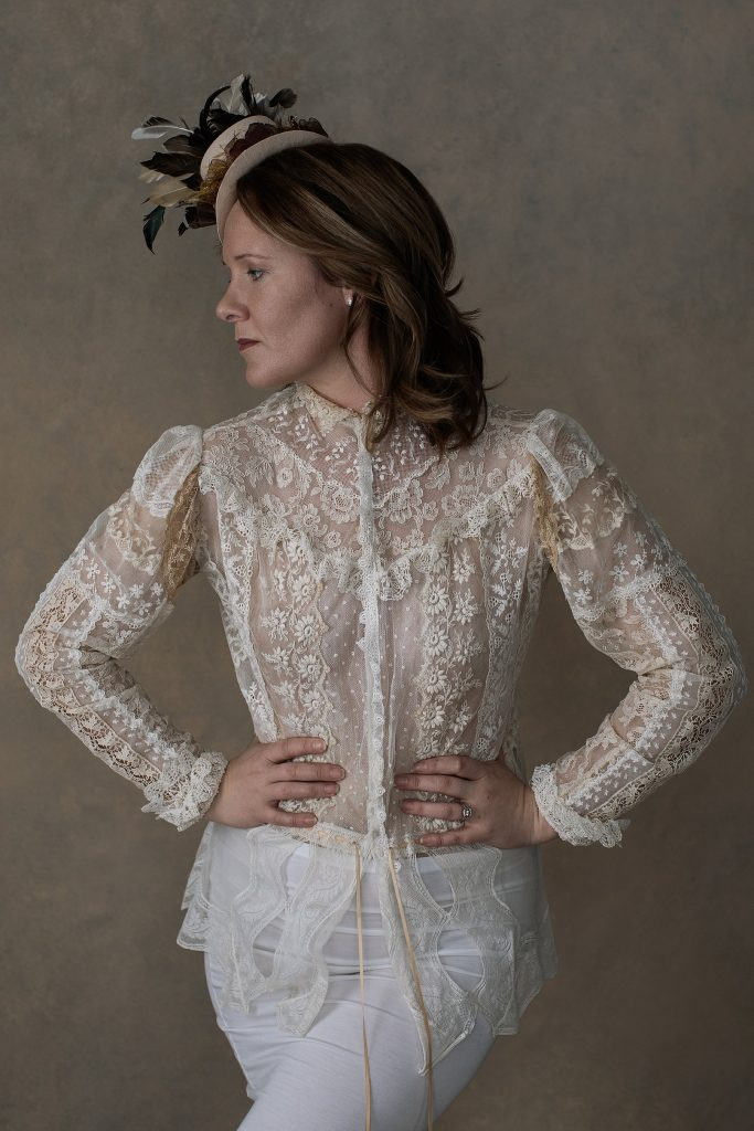 Neutral toned profile portrait of Rebecca in antique lace top and little hat with feathers