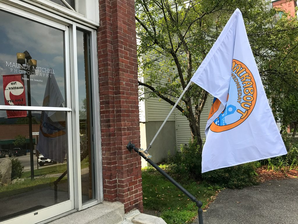 Walkabout Wednesday flag outside Maundy Mitchell Photography studio in downtown Plymouth, New Hampshire