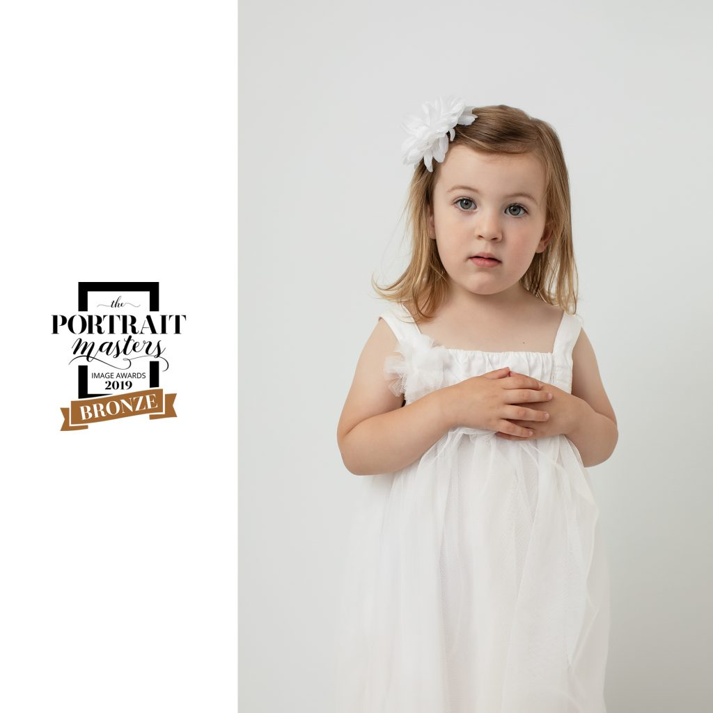 Piper, portrait of young girl in white dress with white background. Bronze award in Children's Portraiture