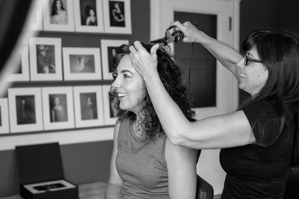 Behind the scenes photo of professional hair and makeup styling before the photo session
