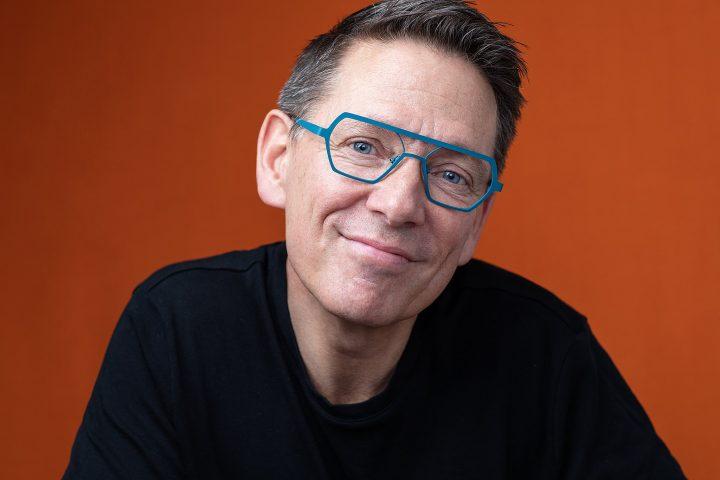 Portrait of Dan Perkins for Artisan Eyewear.  Wearing bold teal frames.  Bright orange background.