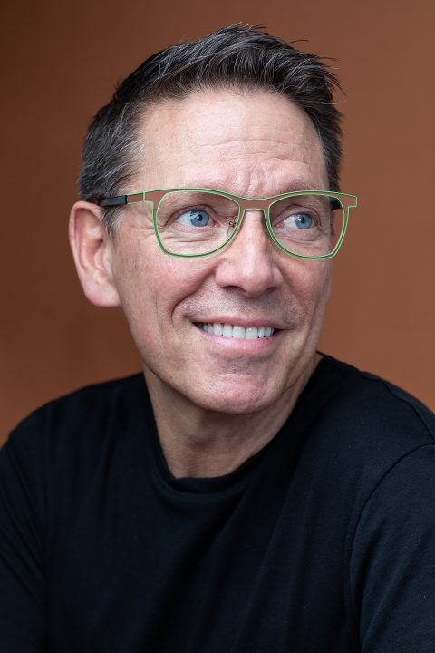 Portrait of Dan Perkins for Artisan Eyewear.  Wearing brown and green frames with brown background.