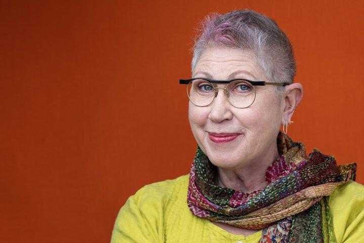 Portrait of Melissa McCarthy for Artisan Eyewear.  Wearing gold eyeglass frames with an orange background.