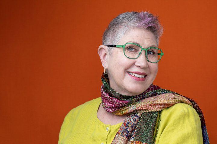 Portrait of Melissa McCarthy for Artisan Eyewear.  Wearing green eyeglass frames with an orange background.