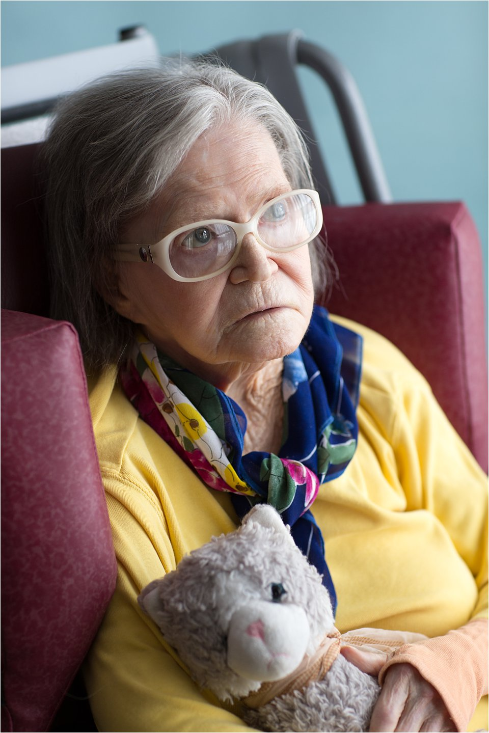 Elderly woman in stylish glasses with stuffed animal (C) Maundy Mitchell