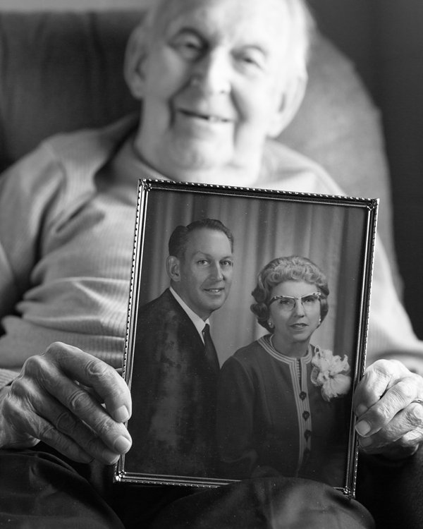 Black & White Portrait of Elderly Man Holding Wedding Photo