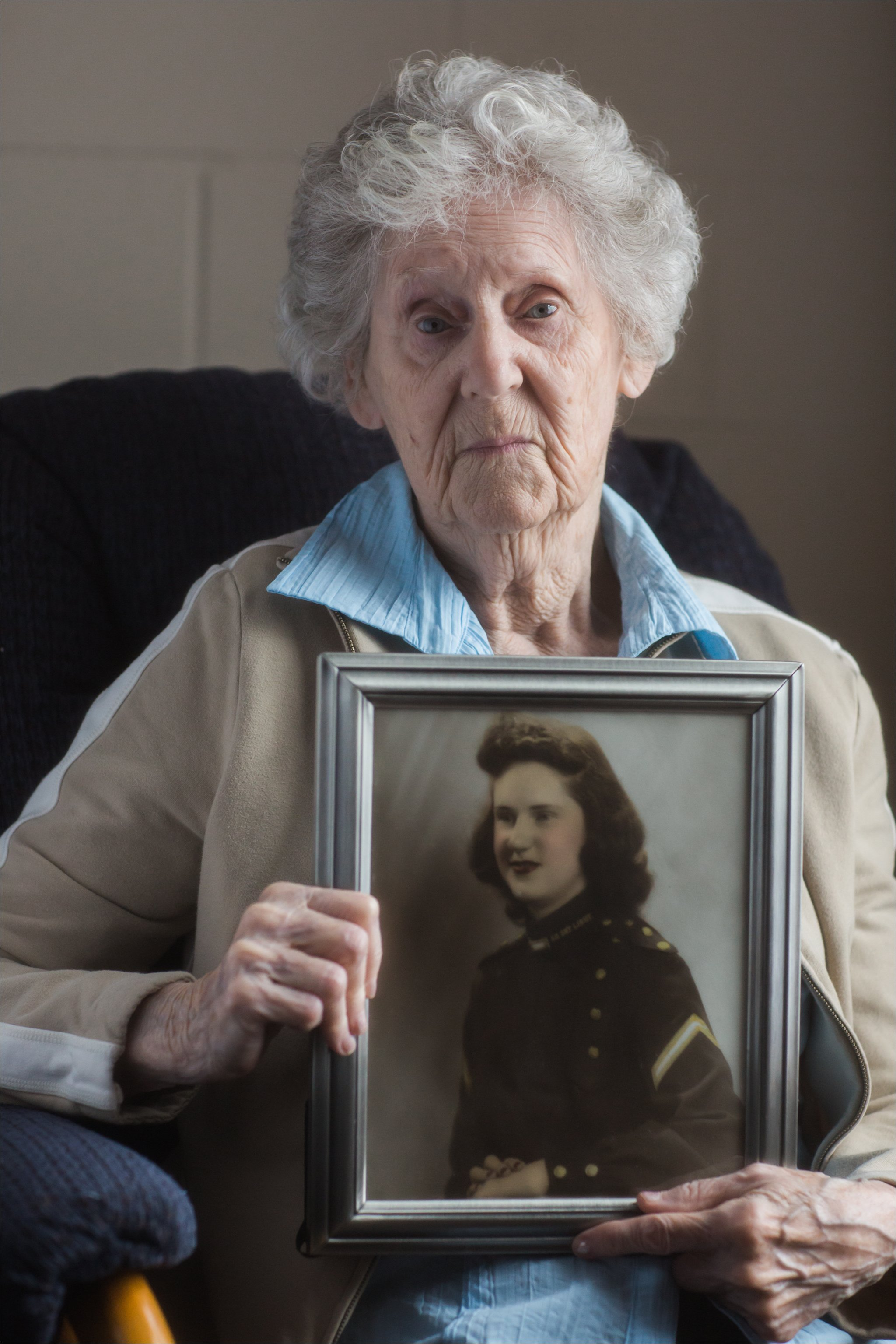 Woman Holding 1940's Military Portrait of Herself