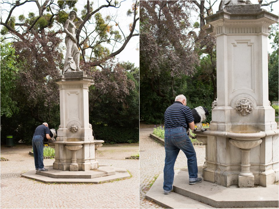 Man Holding Dog to Drinking Fountain (C) Maundy Mitchell