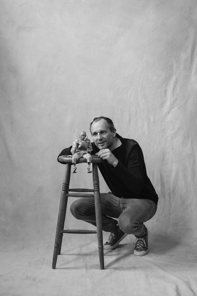 Puppeteer Mark Down, squatting by a stool with a puppet