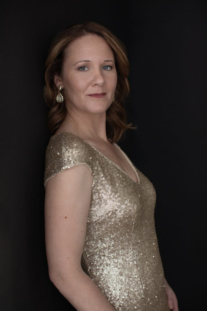 Portrait of Rebecca in a gold gown on a black background