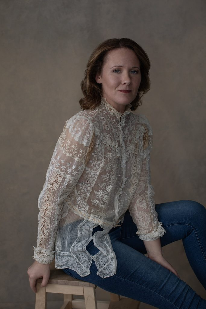 Portrait of Rebecca in antique lace top and jeans.  Neutral tones, Rembrandt lighting, fashion-style pose