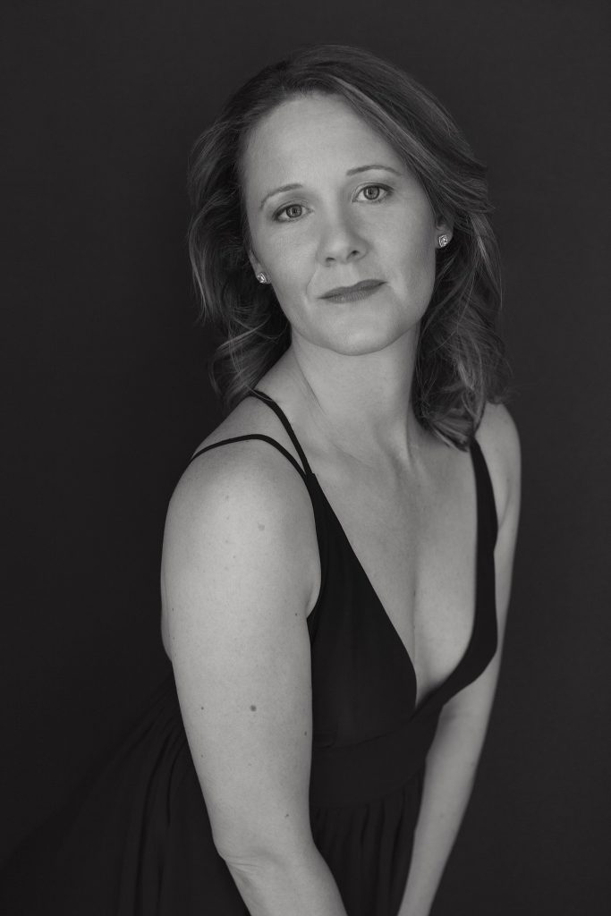Low key, black and white portrait of Rebecca in a black dress