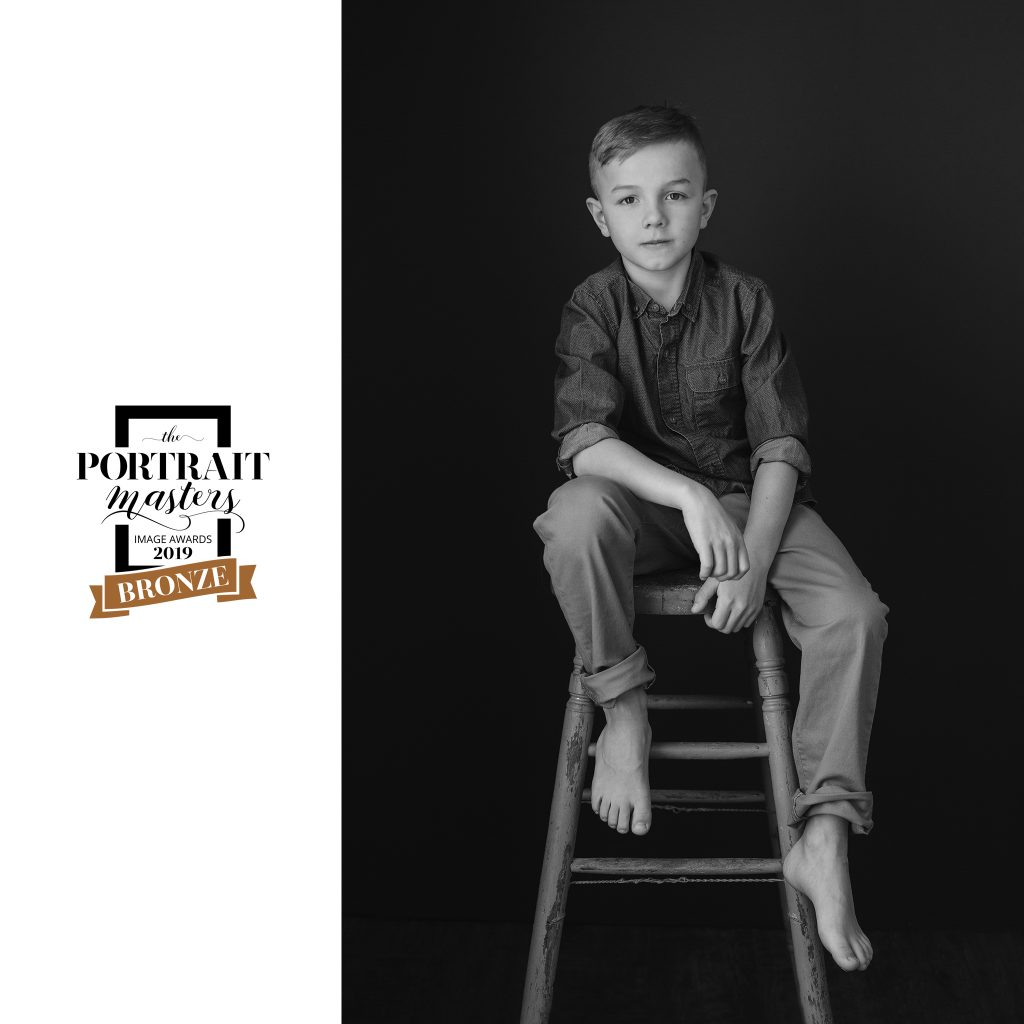 "Black and white portrait of a boy seated on a stool.  Bronze award in children's portraiture. ""Chase"""