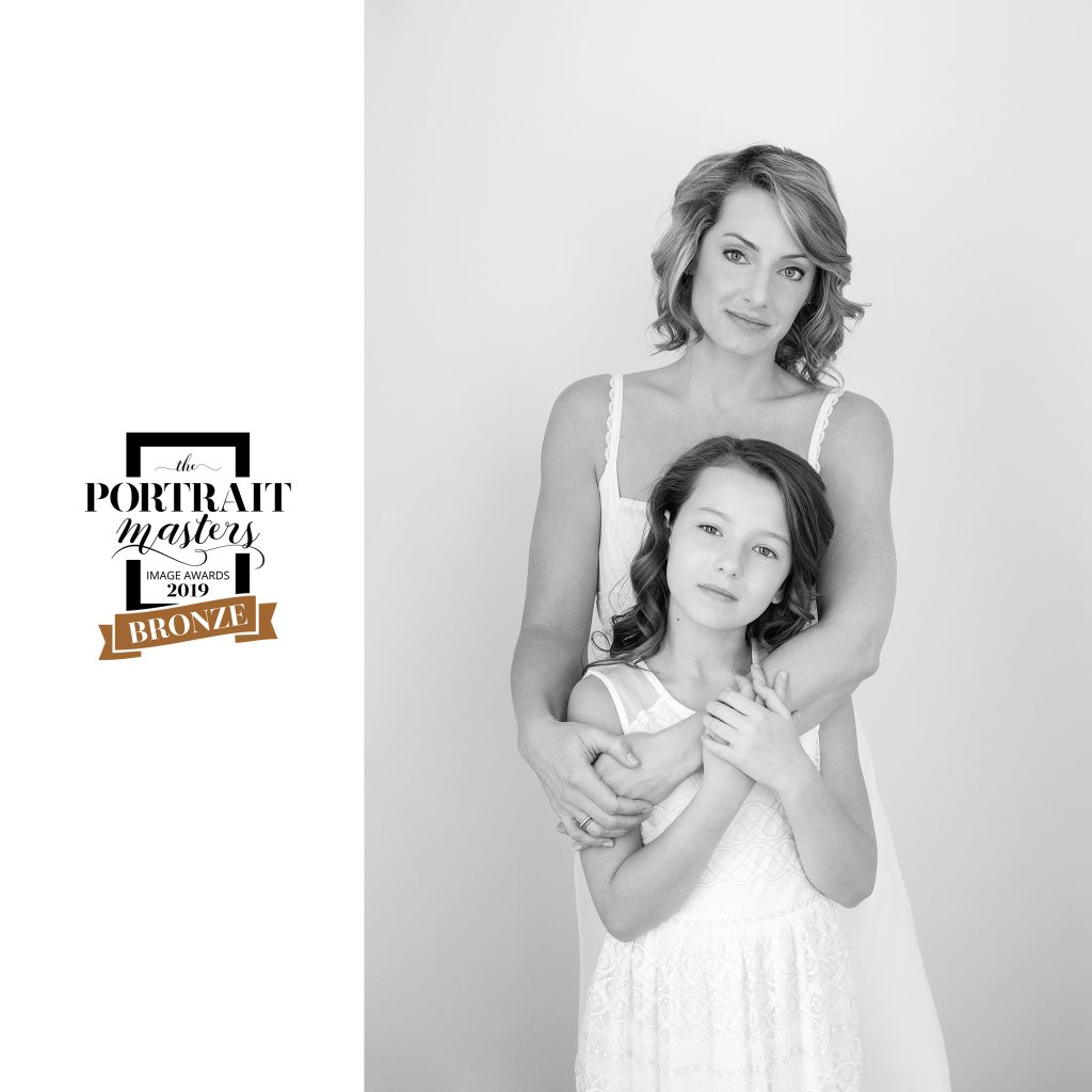 Light colored black and white portrait of mother and daughter. Lisa and Leah.  Bronze award in the Family and group category