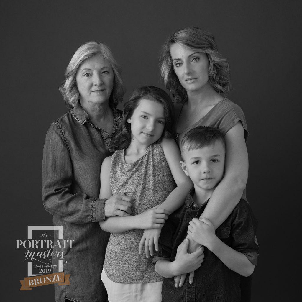 Black and white, three-generation family portrait.  Bronze award in Family portraiture.