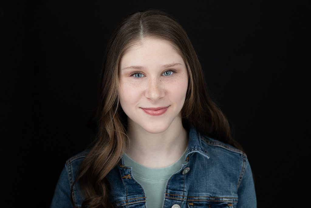 Actor headshot for Sophie Pankhurst in green shirt and jean jacket with black background
