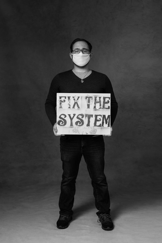 "Black and white portrait of man wearing mask and holding a sign that reads ""Fix the System"""