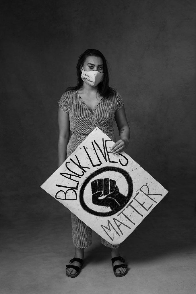 Black and white portrait of woman wearing mask and holding Black Lives Matter sign