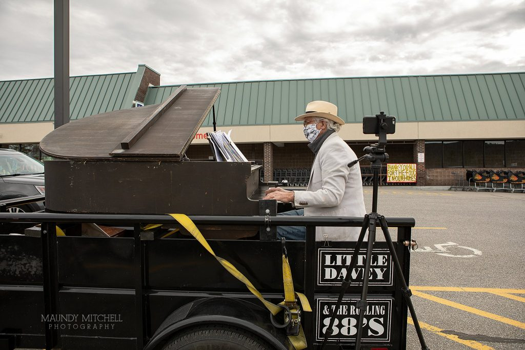 Musician Dave Lockwood sets up his piano and plays in the parking lot of the local grocery store.