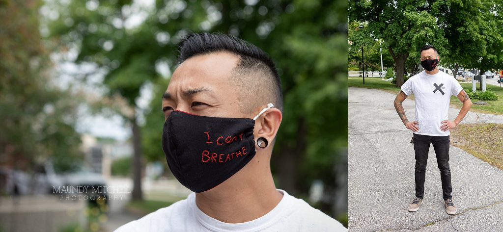 "A man on the sidewalk is wearing a mask that reads ""I can't breathe"""