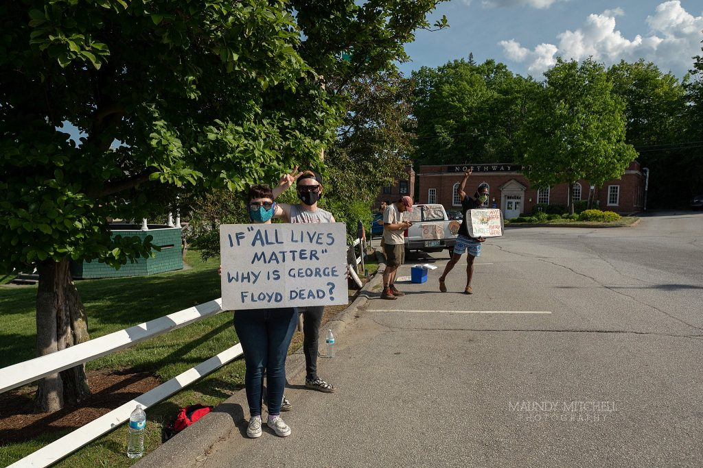 Protesters on the Plymouth, NH town common hold signs.