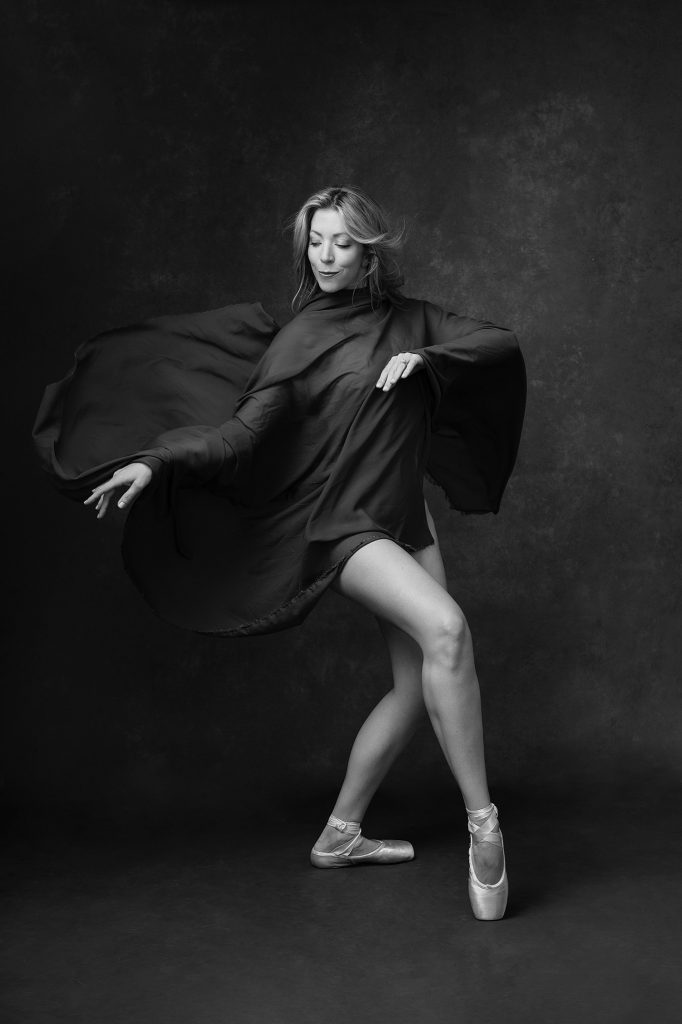 Black and white portrait of dancer in fabric with pointe shoes