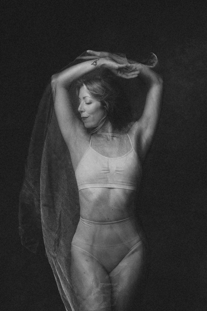 Black and white portrait of dancer in sheer fabric