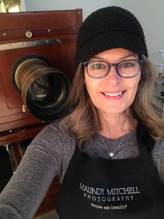 """Selfie"" Maundy Mitchell wearing ""People are beautiful"" apron in her tintype studio with antique camera"