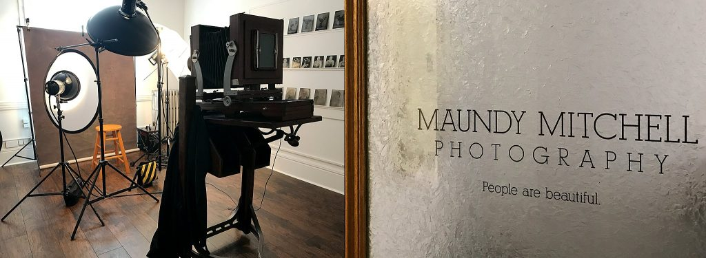 The antique Deardorff 8x10 camera and the tintype studio room's door sticker: Maundy Mitchell Photography - People are beautiful.