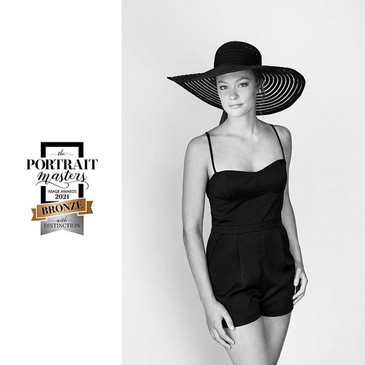 Black and white portrait of teenage girl wearing a wide-brimmed hat and vintage swimsuit
