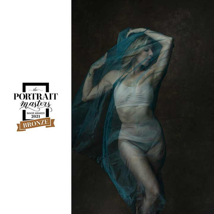 Portrait of dancer wrapped in sheer blue fabric