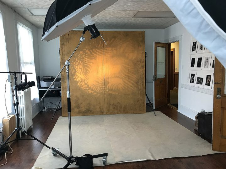 The set with hand-painted gold metallic backdrop and a three-light setup
