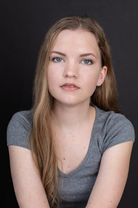 Vertical headshot of Chloe, a young actor, wearing a gray t-shirt and photographed on a black background