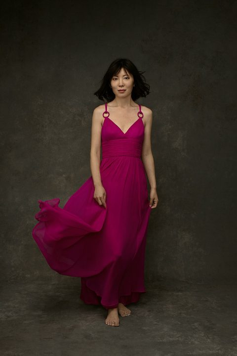 Studio portrait of pianist Zi Liang in pink flowy dress