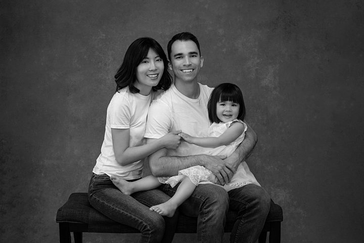 Black and white studio portrait of a family with young daughter in Plymouth, NH.