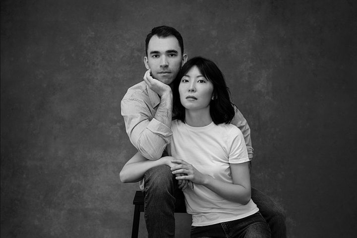 Black and white portrait of piano duo Zi Liang and husband Adam Mayon, wearing casual clothing