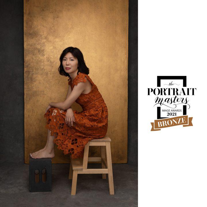 Portrait of Zi, seated, wearing orange lace dress in front of metallic gold backdrop - Bronze Award